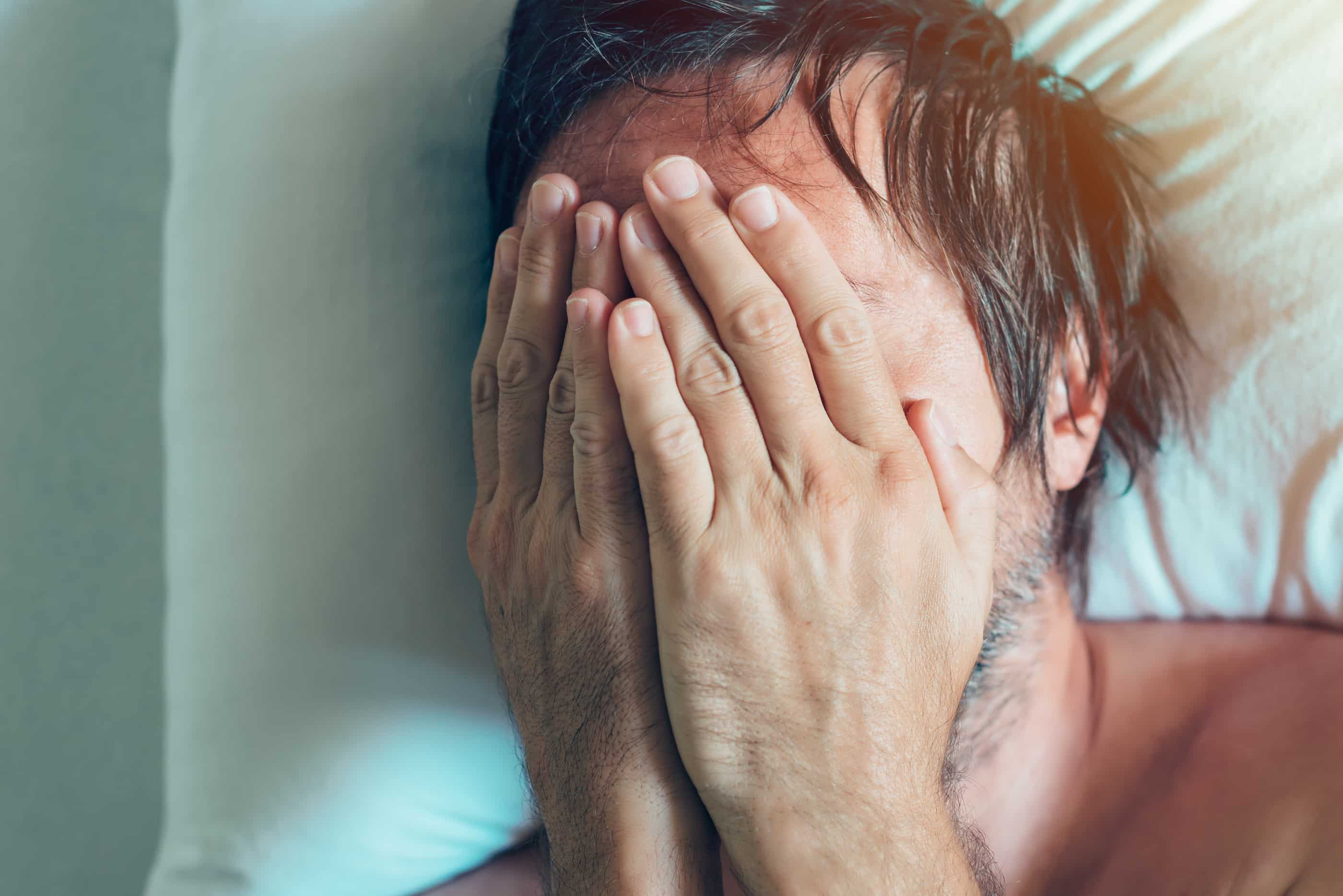 Man holding his face while suffering from opioid withdrawal