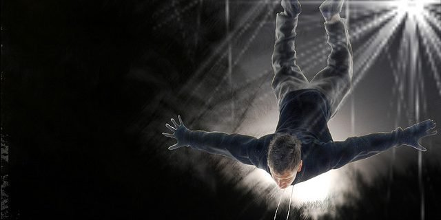 Man falling from the sky head first with arms out with spotlight on black background