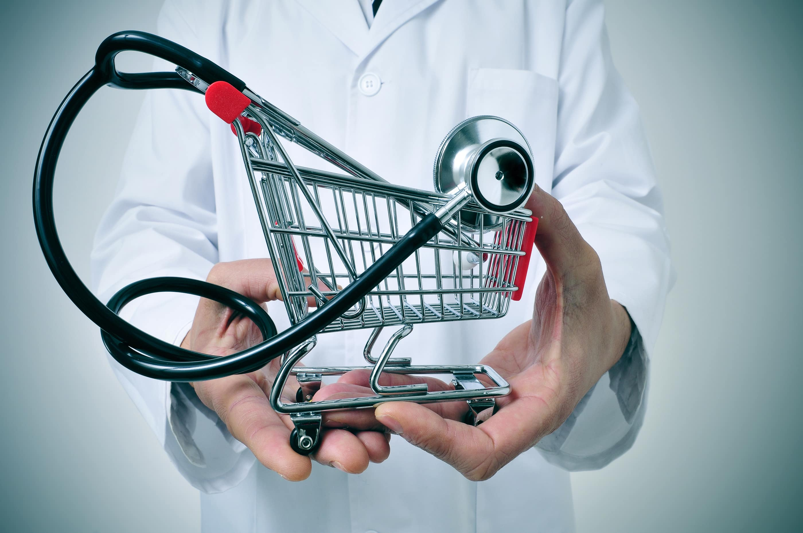 doctor holding in his hand a shopping cart with a stethoscope inside, depicting the health care industry concept