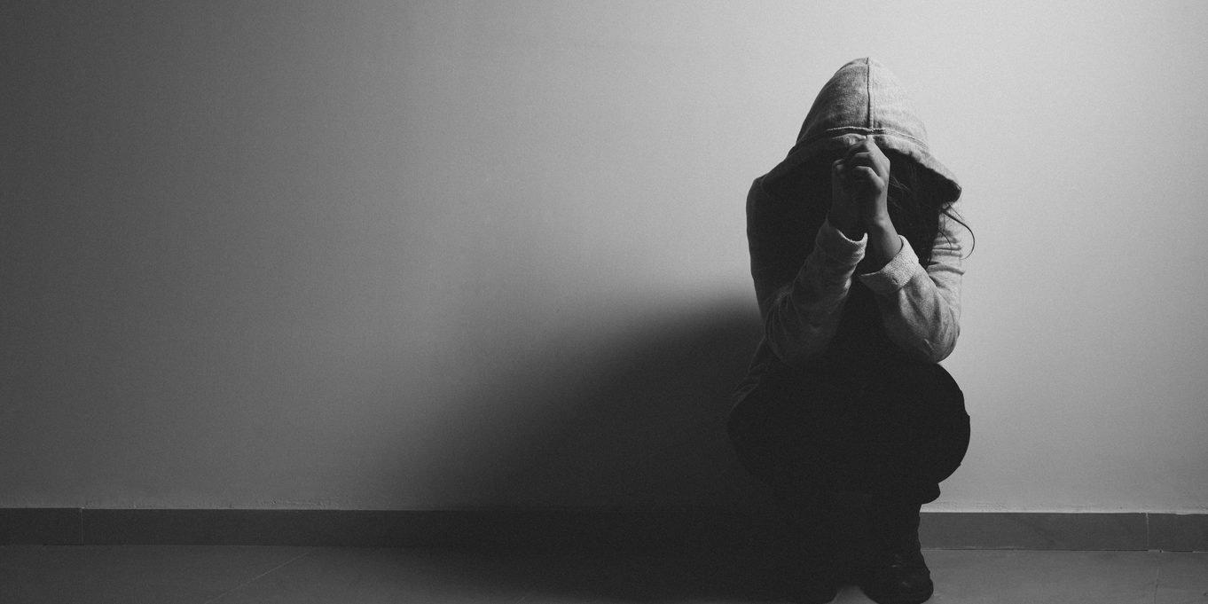 Woman crouched down looking depressed which possibly occured from being called addict